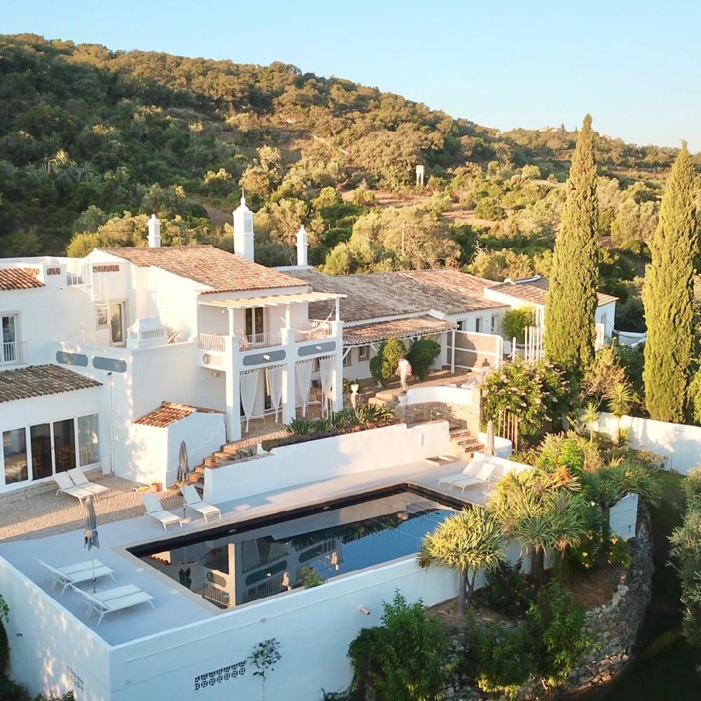 Luchtview van wit landhuis met zwembad en veel groen