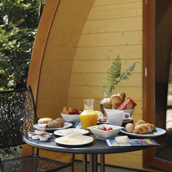 Ontbijt op de veranda van de pod, in het bos