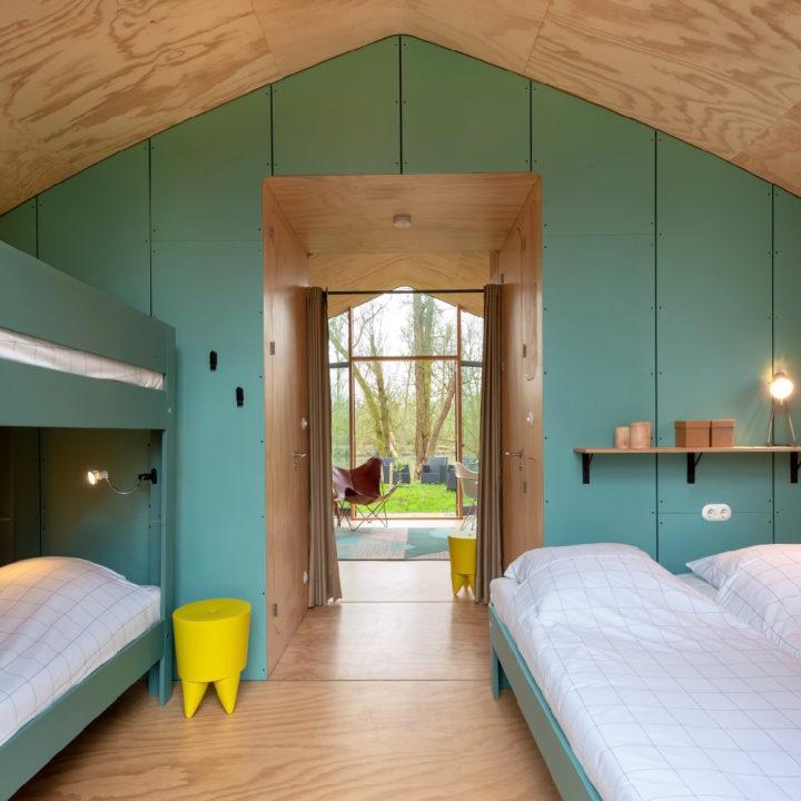 Kartonnen vakantiehuis met doorkijk van de slaapkamer naar de zithoek
