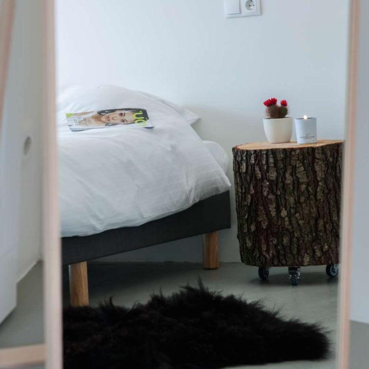 Bed met houten kolos ernaast als nachtkastje