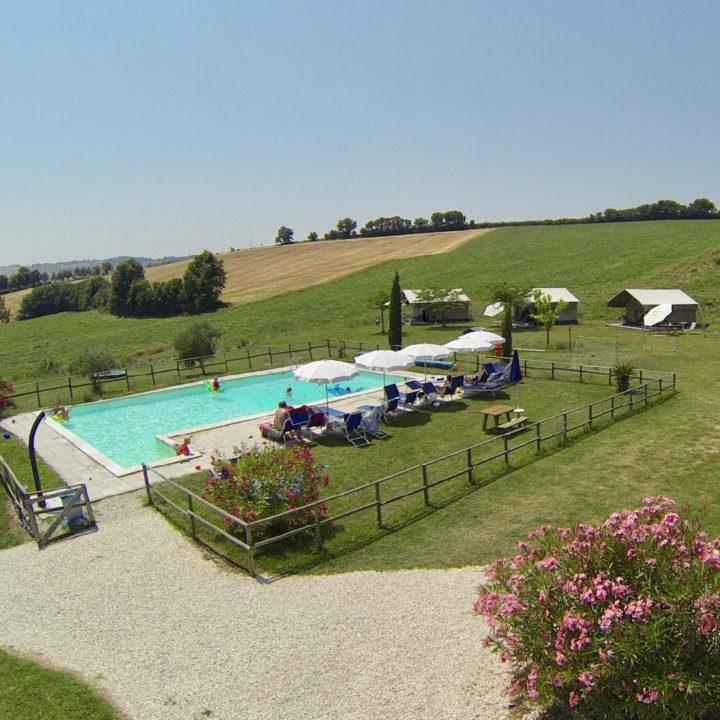 Overzicht van een zwembad met ligstoelen en parasols en safaritenten