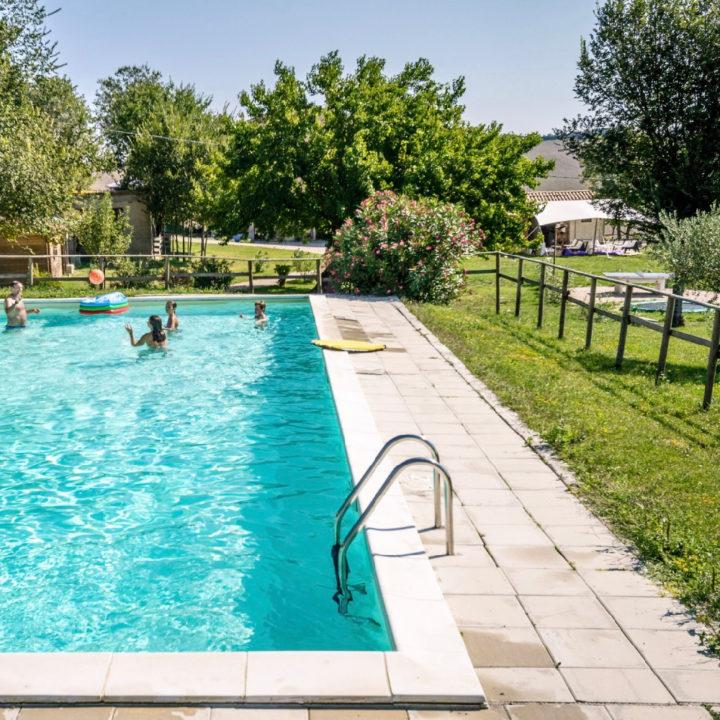 Zwembad met spelende kinderen en een zonneweide