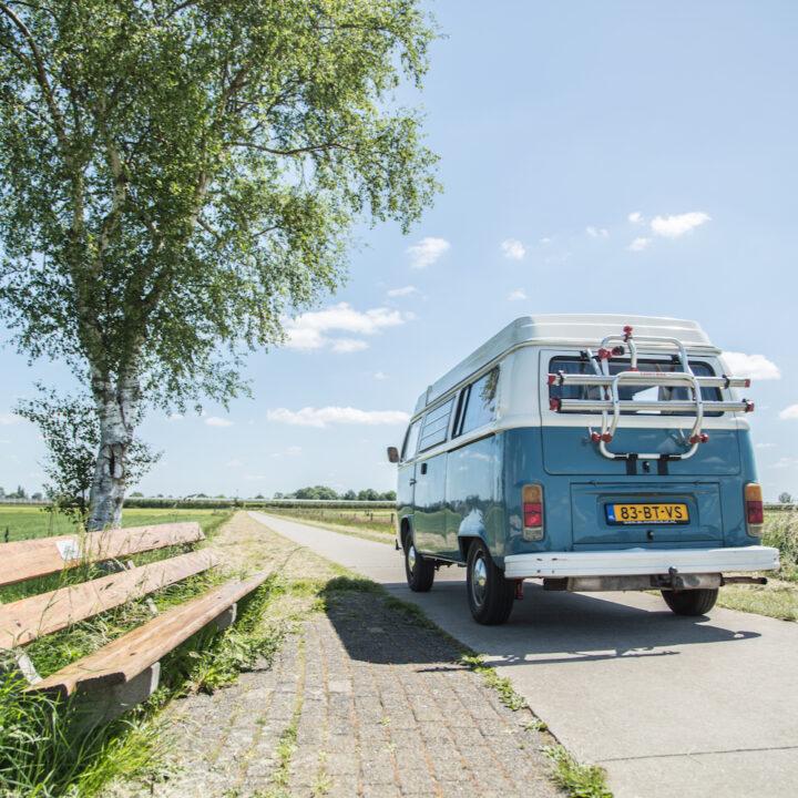 Blauw busje op een landweg