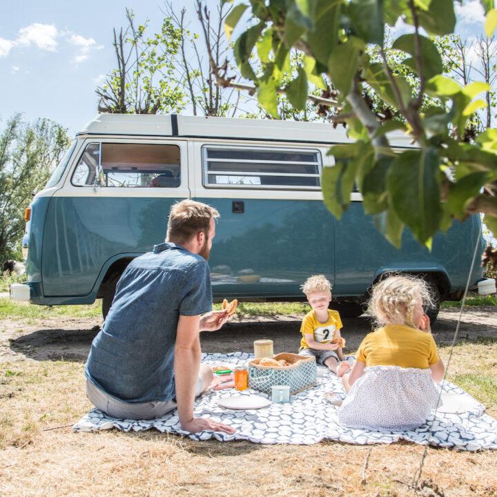Gezin aan het picknicken bij een Blauw Volkswagen Busje