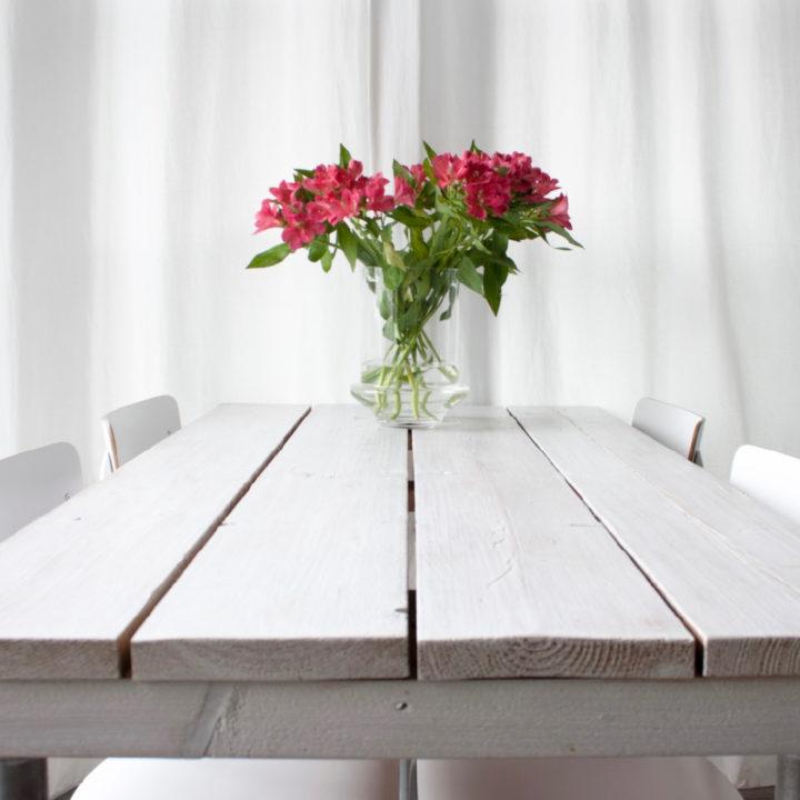 Witte houten eettafel met vier witte stoelen