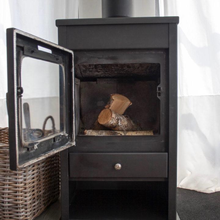 Zwarte houtkachel met openstaande deur en houtblokken