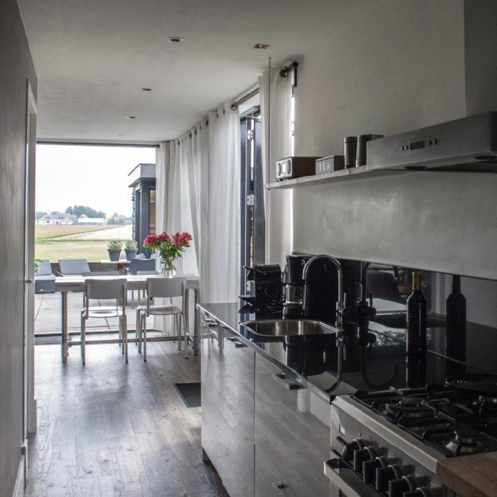 Keukenblok met op de achtergrond de eethoek met witte tafel en stoelen