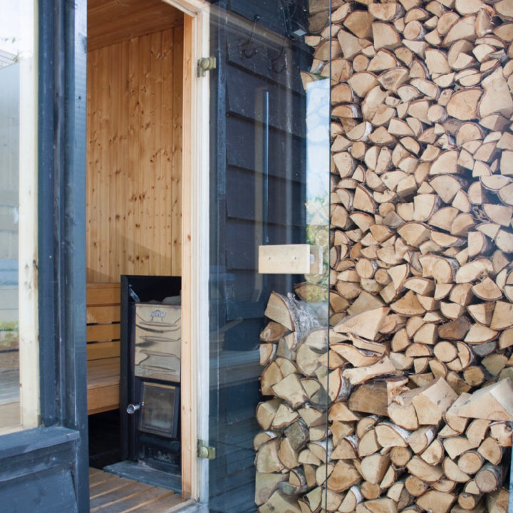 Sauna met voorraad hout naast de deur