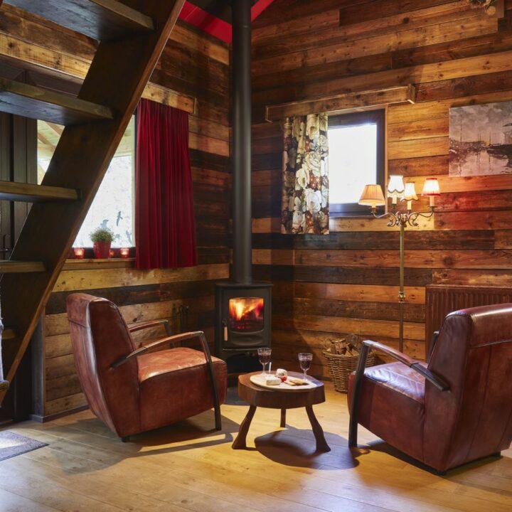 Twee leren fauteuils bij de houtkachel in de cabin