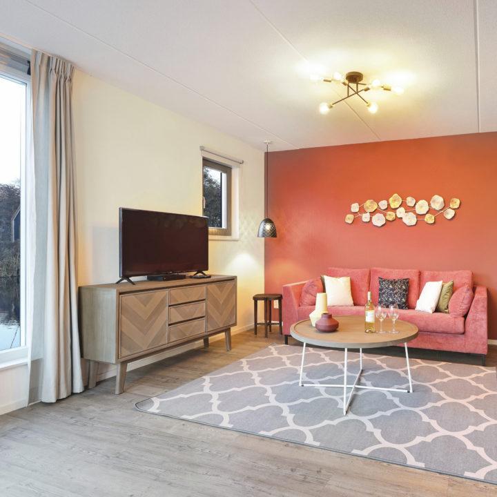 Woonkamer met lekker vloerkleed, roze bank en roze muur in vakantiehuis van Landal