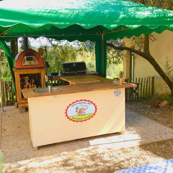 Groene parasol met daaronder een pizza oven en keukenblok