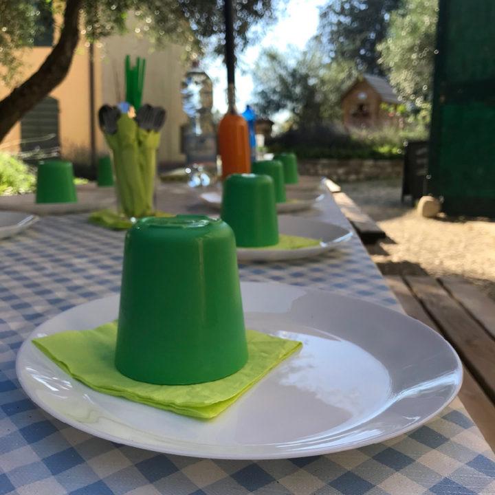 Gedekte tafel met witte borden en groene plastic bekertjes erop