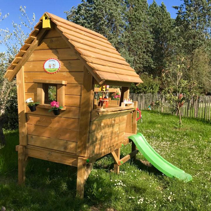 Houten speelhuisje met groene glijbaan, op een grasveld