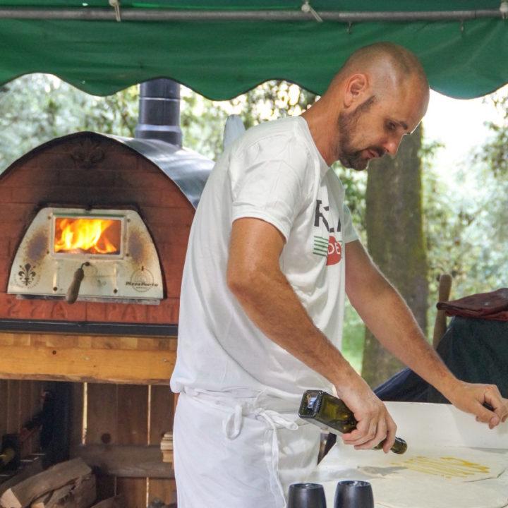 Pizza avond met vuurtje erin en pizza bakker met olijfolie in hand