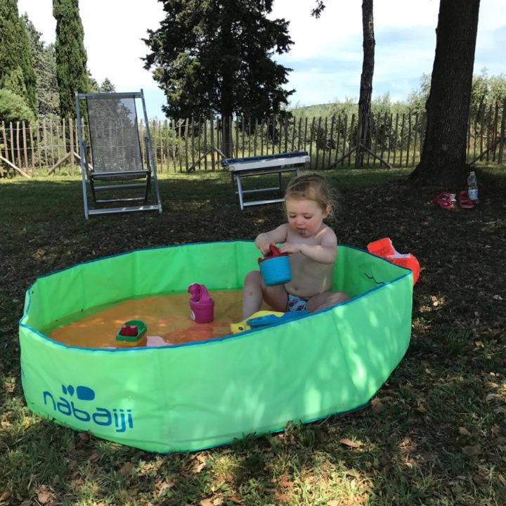 Groen peuterbadje in de schaduw met spelend meisje