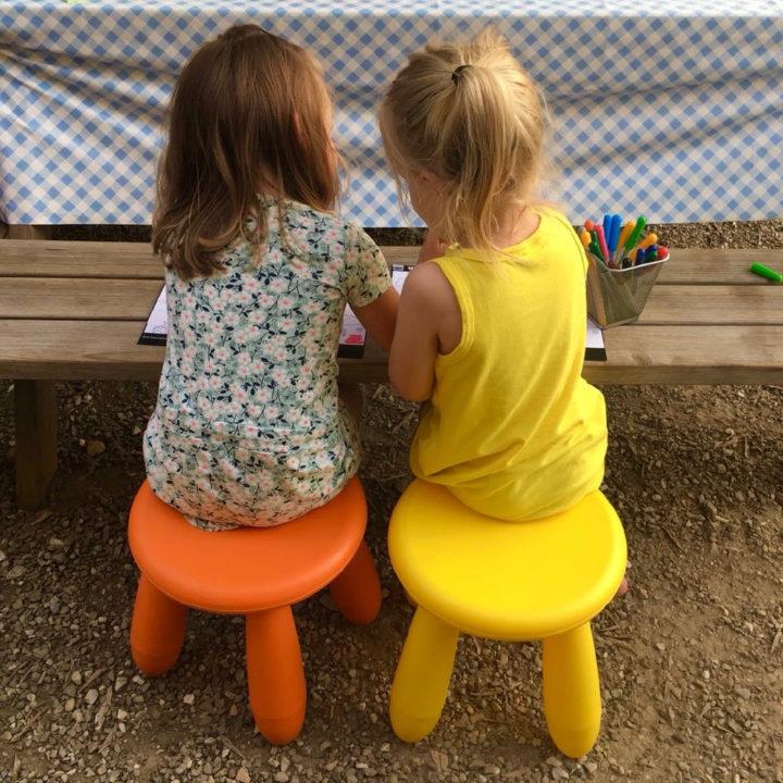 Twee meisjes op gekleurde krukjes zitten te tekenen aan een houten tafel