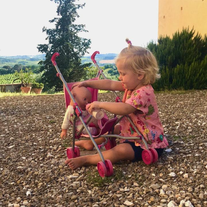 Een klein meisje speelt met een pop in een poppenwagentje