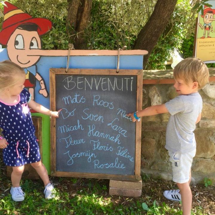 Een krijtbord met twee kinderen ernaast en Pinokkio.