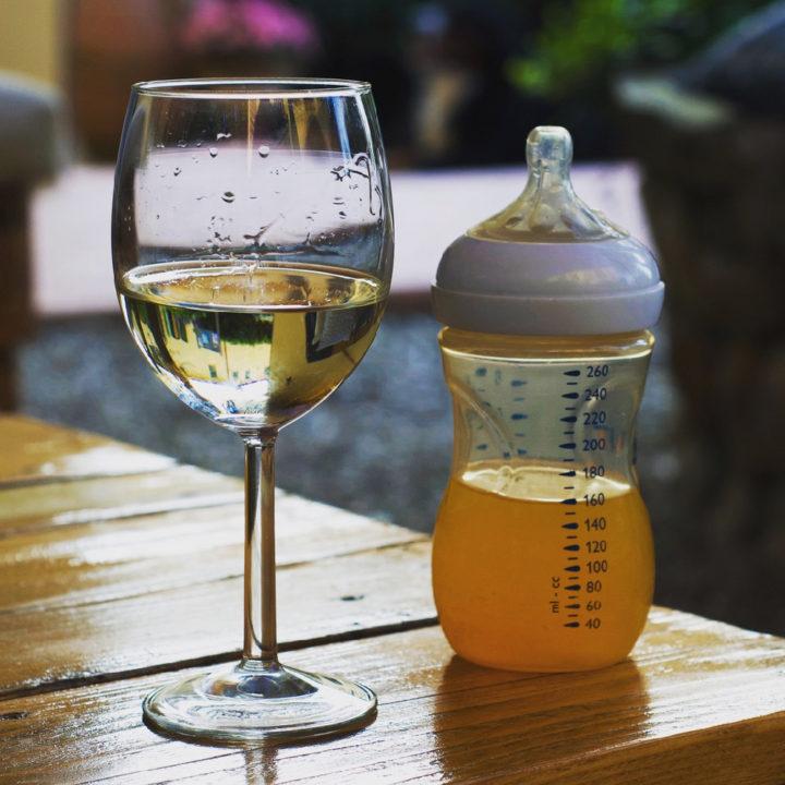 Een glas wijn op een tafeltje met daarnaast een babyflesje met een sapje erin