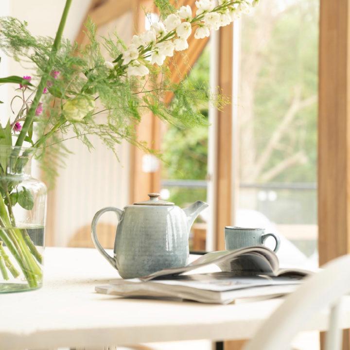 Theepot met tijdschrift op tafel van een vakantiehuis in Egmond
