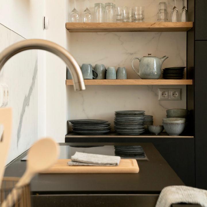 Zwarte keuken met servieskast in een vakantiehuis in Egmond