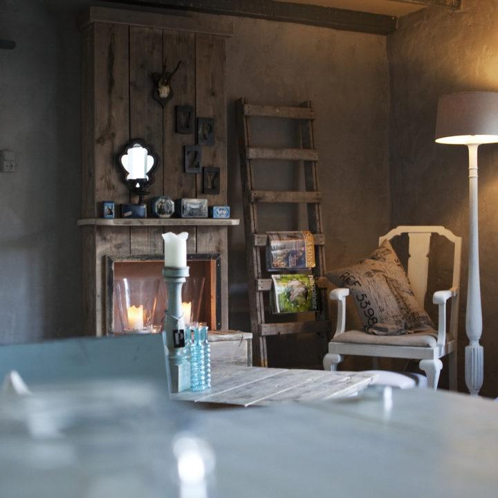 Brocante kamer met fauteuil, brandende kaarsen, schouw van steigerhout