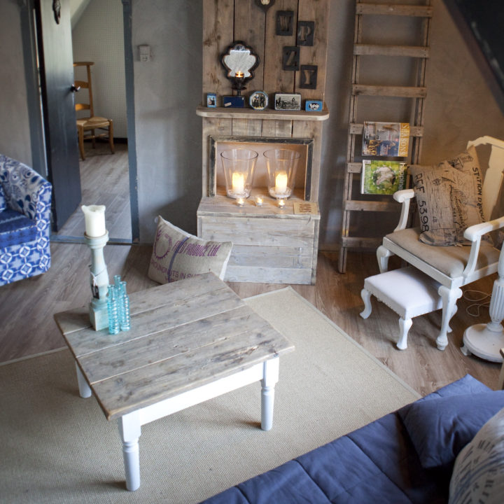 Overzicht kamer met tafel, stoelen en schouw met brandende kaarsen