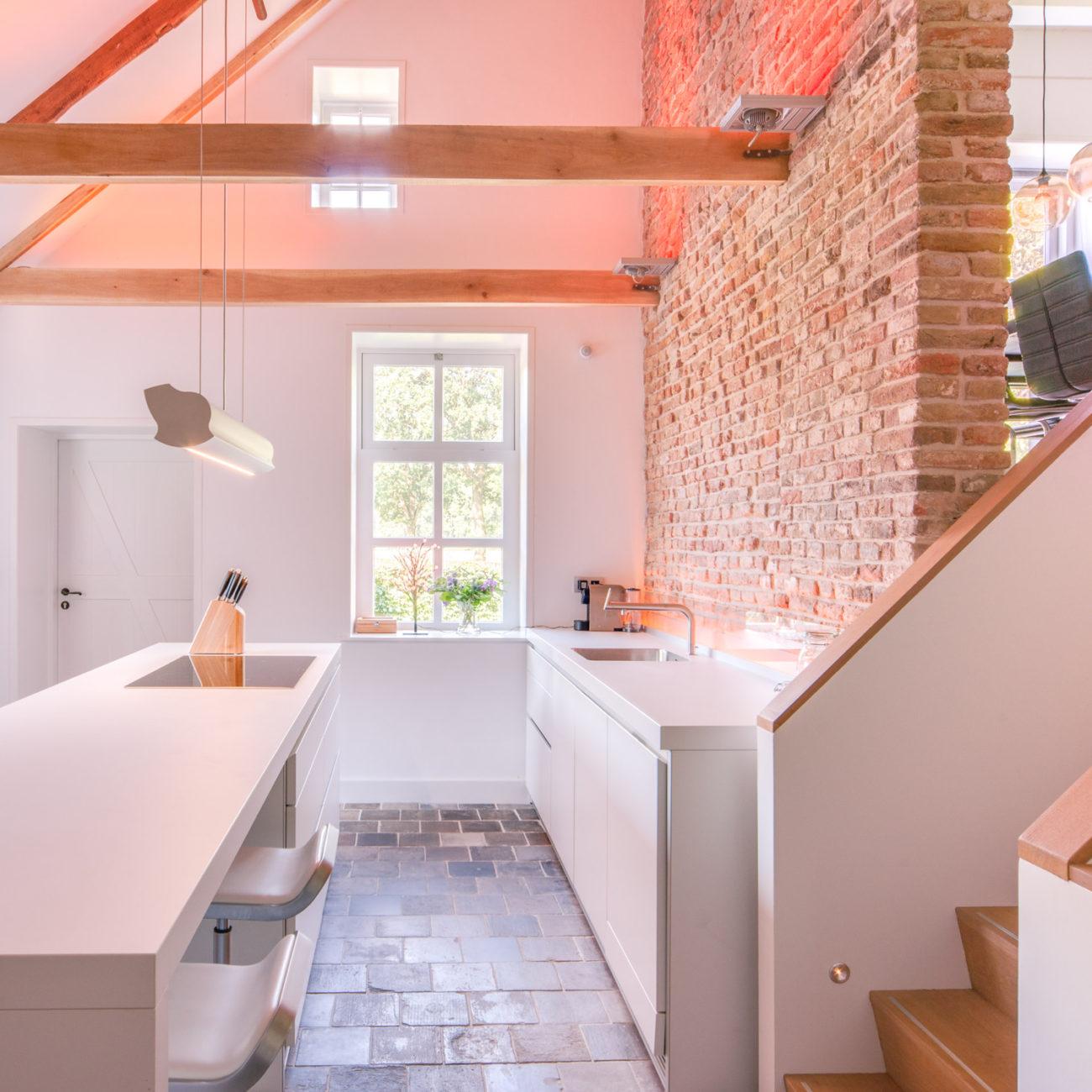 Strakke witte keuken met authentieke tegelvloer