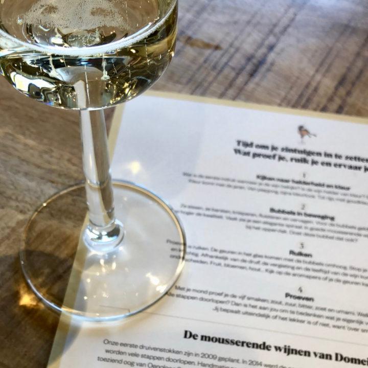 Een glas mousserende wijn op tafel bij Domein Holset