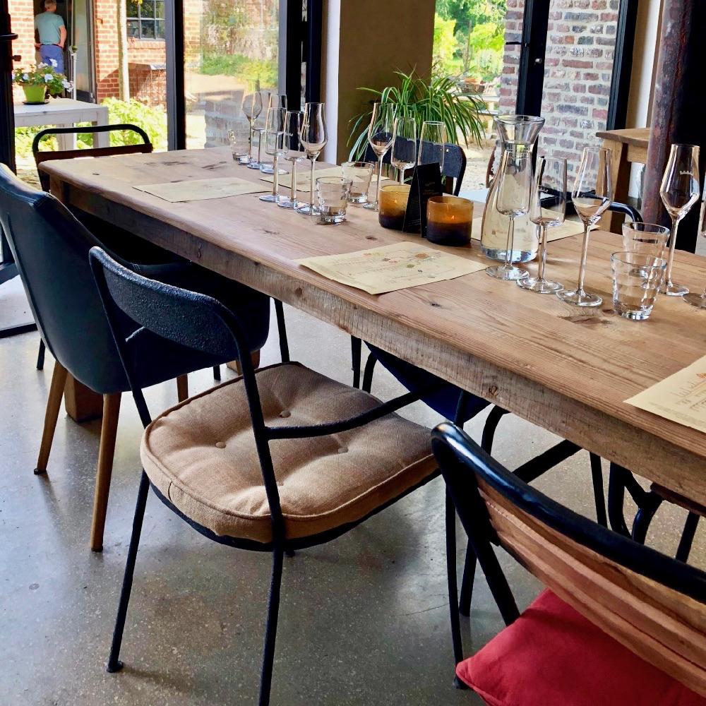 Een tafel met verschillende stoelen en op tafel wijnglazen voor een wijnproeverij