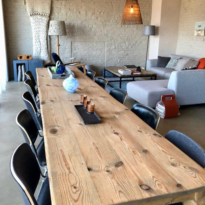 Een lange eettafel met zwarte stoelen en op de achtergrond een grijze hoekbank