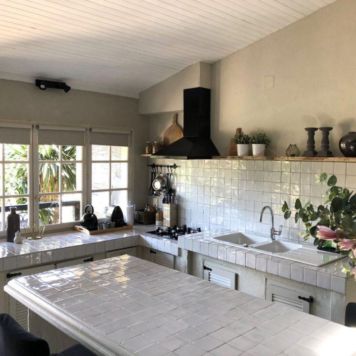 Wit getegelde keuken met kleine raampjes