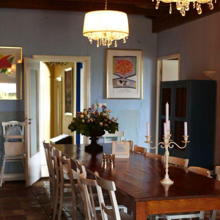 Lange houten tafel met witte stoelen en kandelaar