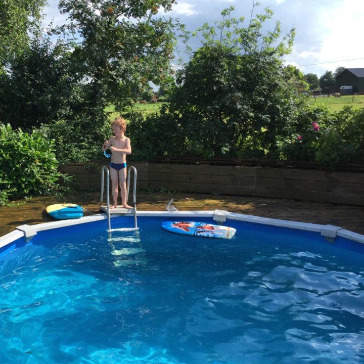 Een rond opzet zwembad met een jongetje op het trappetje