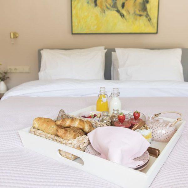 Tweepersoons bed met zacht roze sprei en wit dienblad met ontbijt lekkers
