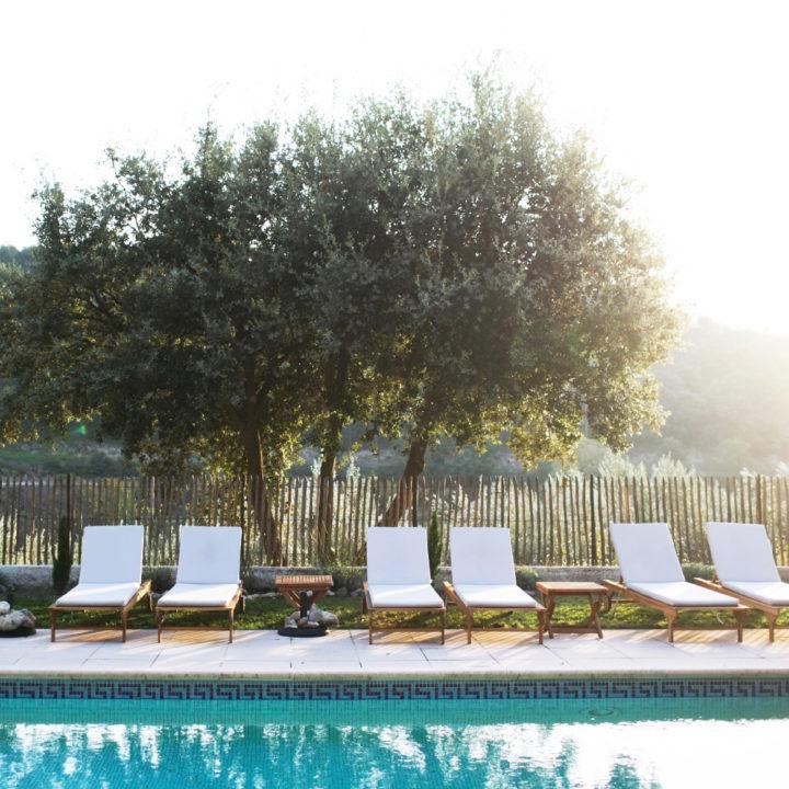 Ligbedden met witte kussens aan de rand van het zwembad, in het zachte ochtendlicht