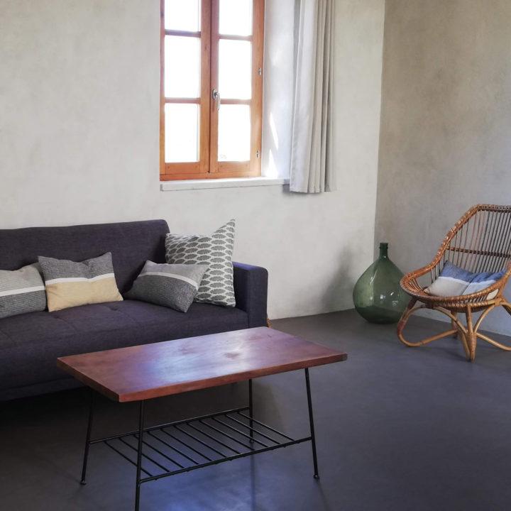 Grijze bank met rotan stoeltje in een vakantiehuisje in Frankrijk