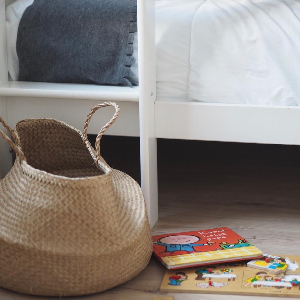 Een mand op de grond voor een stapelbed met leesboekjes ernaast