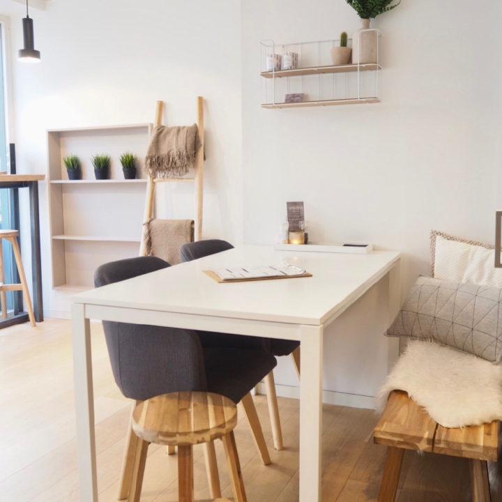 Tafel met twee zwarte stoelen en een bankje met kussens