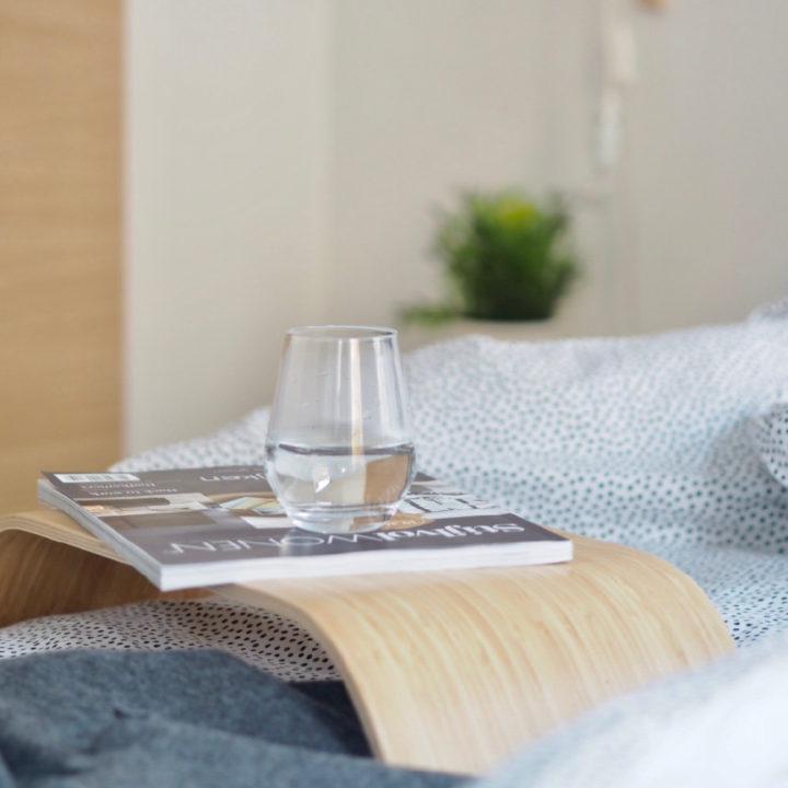 Bed met houten tafeltje erop met tijdschrift en glas water