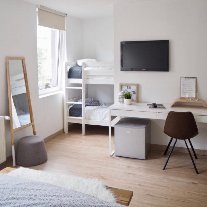 Hotelkamer met wit bureau en wit stapelbed