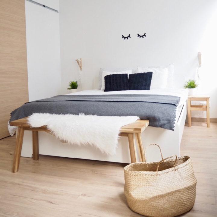 Tweepersoons bed met rieten mand op grond er voor