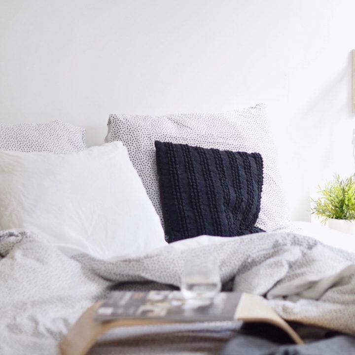 Bed met witte, zwarte en gestipte kussens