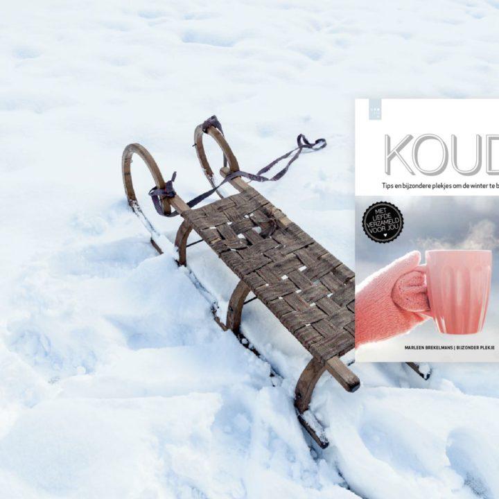 Een slee in de sneeuw met daarbij de cover van het boek KOUD