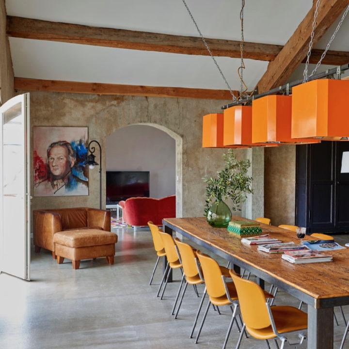 Lange eettafel met oranje lampen erboven