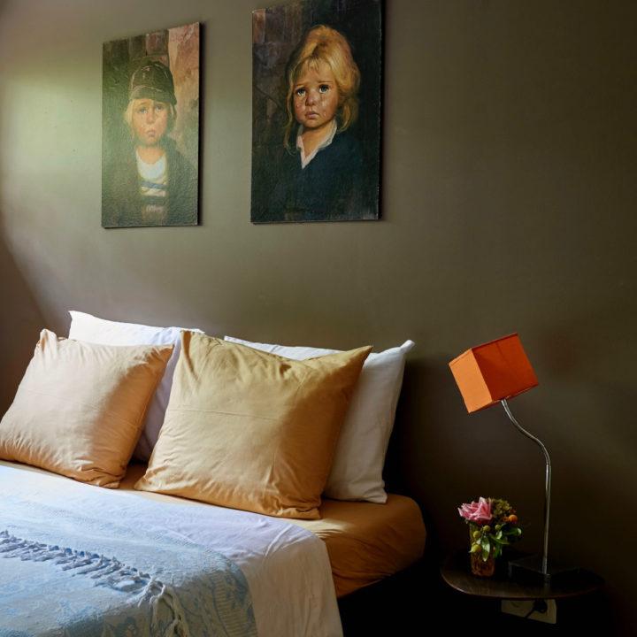 Slaapkamer met tweepersoons bed, 2 schilderijen aan de muur, oranje lampen op het nachtkastje