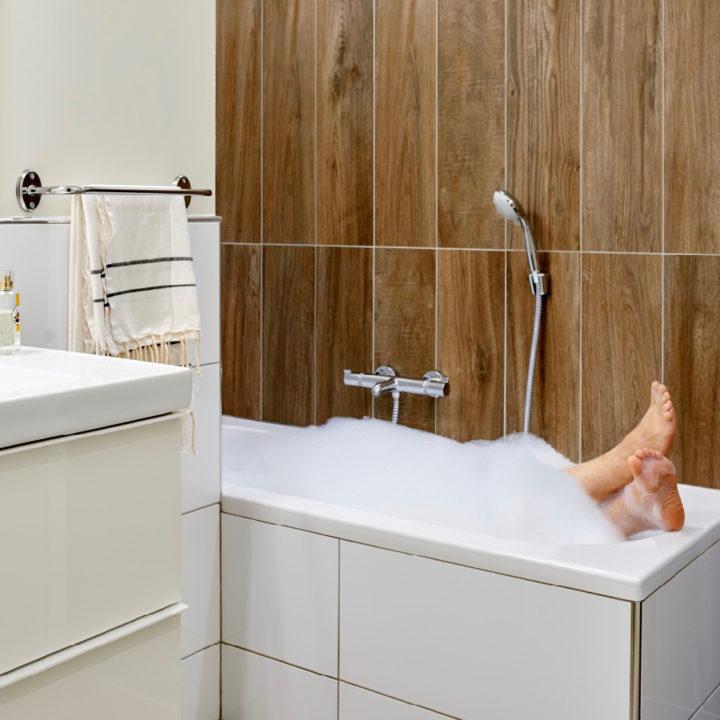 Badkamer met ligbad met een laag schuim en voeten die er uit steken