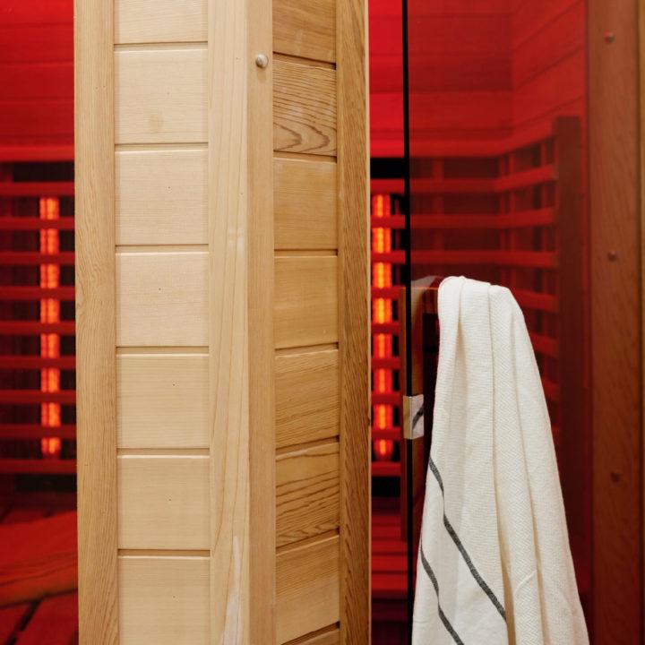 Sauna met rode lampen en een badjas aan de deur
