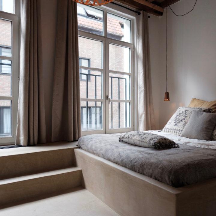 Slaapkamer met hoge ramen bij Zalig in Antwerpen