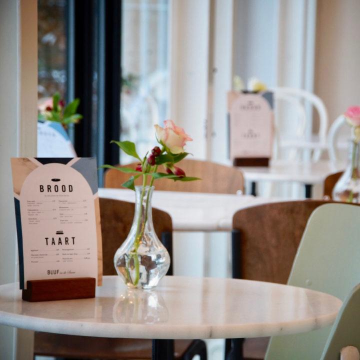 Ronde tafels, mintkleurige stoelen en de menukaart op tafel